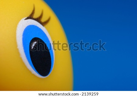 rubber duck toy with closeup of  its eye - stock photo