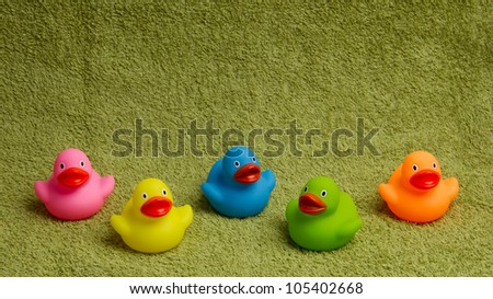 Rubber ducks isolated on a green towel, with room for text