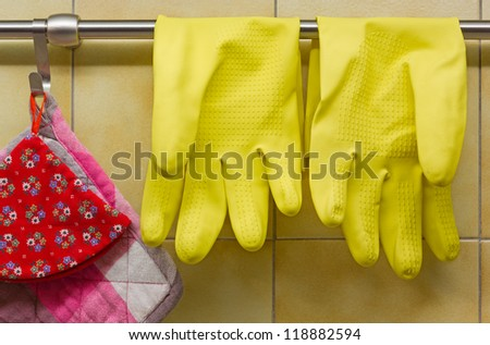 Rubber Gloves and Pot Holders Against Kitchen's Wall