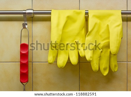 Rubber Gloves and Red Handled Tool Against Kitchen's Wall