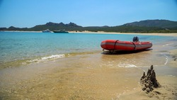 Rubber inflatable motor boat of red color, moored on a beautiful sandy beach with clear and transparent blue water. Sand castle on the beach. Rest by the sea on the islands Luxury yachts off the coast