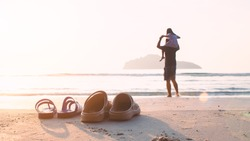Rubber slippers on the beach with freedom father and daughter standing and watching the sunrise.16:9 style