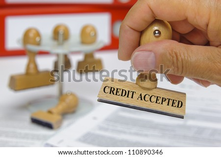 rubber stamp in hand marked with credit accepted