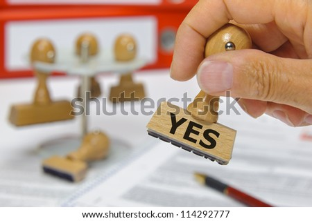 rubber stamp in hand marked with yes