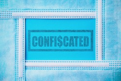 Rubber stamp with text confiscated in an abstract frame made of medical surgical masks on a classic blue background