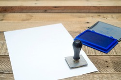 Rubber Stamp with the blue ink place on the white paper and copy space for your text.