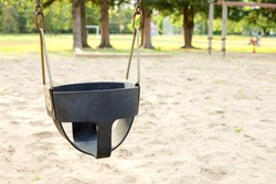 Rubber swing on chains for little children with sand underneath in the park playground with sand underneath, trees and field in the background