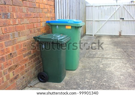 Rubbish and recycle bins in a typical suburban backyard in australia