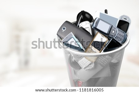 Rubbish bin full of old cellphones stock photo