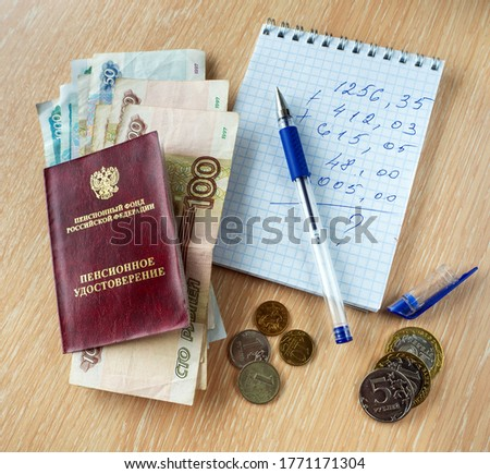Ruble denominations are under the pension certificate of the Russian Federation. On the table is a notebook with calculations, a pen and coins.