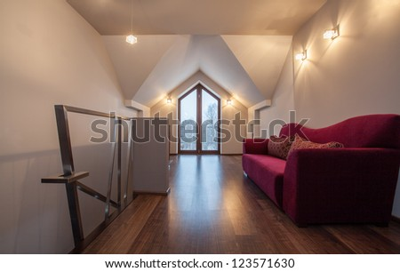 Ruby house - Couch in corridor next to staircase, modern interior - stock photo