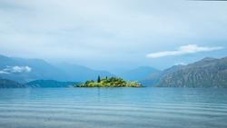 Ruby Island on Lake Wanaka with background mountains in the mist, Otago Region, South Island, New Zealand