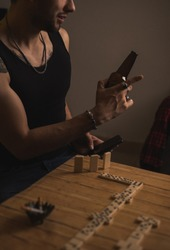 Rude young man playing dominoes with his friends, drinking beer while talking and laughing with his friends, on the table are dominoes, cigarettes, and in his hand he is carrying multiple rings