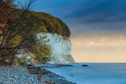 Ruegen Island at Jasmund National Park. Coastline with chalk cliffs with stony beach in the morning. Autumn mood with deciduous trees and clouds and calm sea