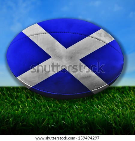 Rugby ball with Scotland flag over grass