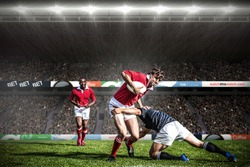 Rugby fans in arena against rugby players tackling during game
