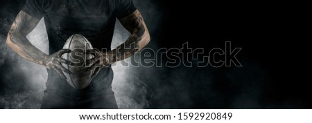 Rugby football player holds ball. Sports banner. Horizontal copy space background Сток-фото ©