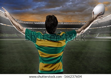 Rugby player in a green and gold uniform celebrating on a stadium.