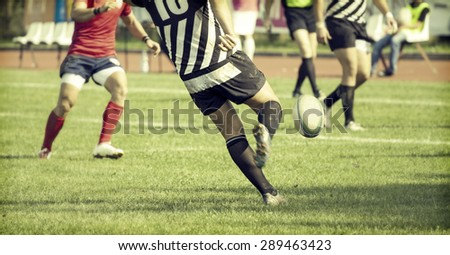rugby player kicking hard the...
