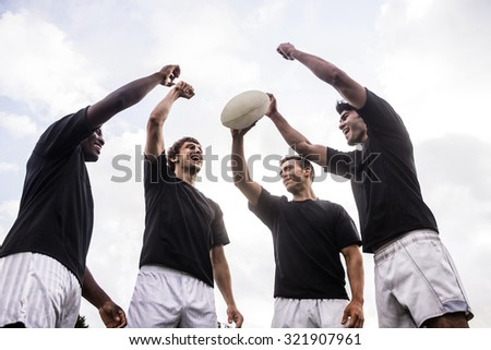 Rugby players cheering together with ball at the park