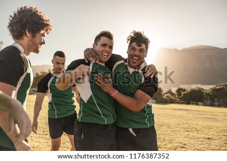 Rugby players hugging and appreciating performance of the teammate after the game. Men in sports uniform celebrating victory of rugby game.