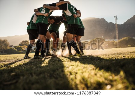 Rugby players in a huddle rubbing their feet on grass. Rugby team showing aggression after the win. #1176387349