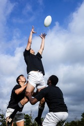 Rugby players jumping for line out at the park