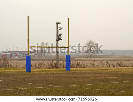 Rugby poles in a rugby field, with tree in the background