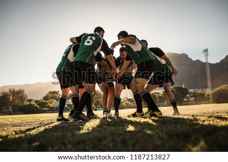 Rugby team putting their hands together after victory. Rugby players cheering and celebrating win.