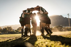 Rugby team standing in a huddle and rubbing their feet on ground. Rugby team celebrating victory.
