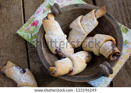 Rugelach with Raspberry jam filling in an old bowl on the wooden table