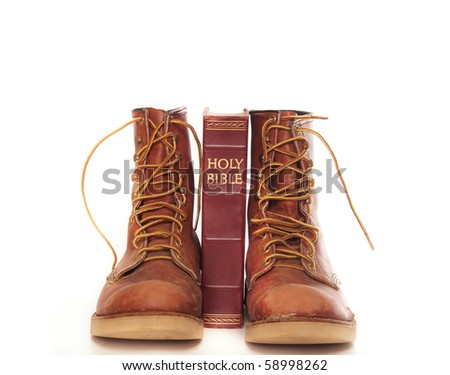 Rugged boots and bible isolated against white