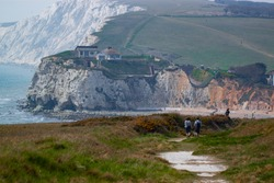 Rugged coastline of Isle of Wight featuring Freshwater bay, promontories, cliffs and beaches. A couple os hiking on the hill on a trail among vast grasslands. There is a house on top of the cliffs.