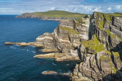 Rugged coastline with majestic tall Kerry Cliffs and turquoise coloured Atlantic Ocean on a sunny summer day, Portmagee, Ring of Kerry, Ireland