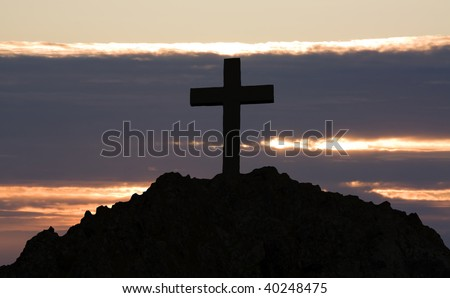 rugged cross silhouette as the sunsets or sunrise