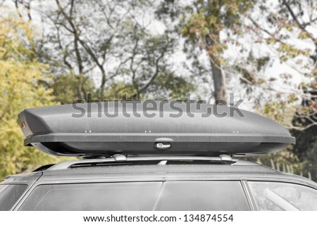 Rugged, grey car rooftop cargo box for nature travel adventure. Car roof rack with grey storage container. Trees, wilderness in the background. Profile, horizontal scene.