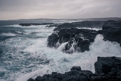Rugged Icelandic coastline with big  waves hitting the black rocks at overcast evening in south west Iceland.