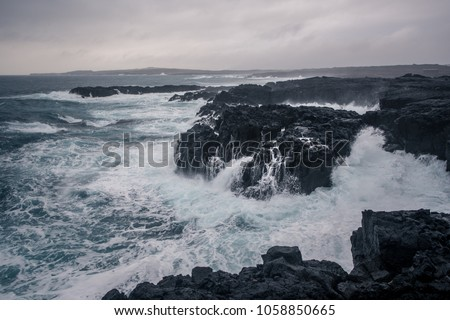 Rugged Icelandic coastline with big  waves hitting the black rocks at overcast evening in south west Iceland. #1058850665