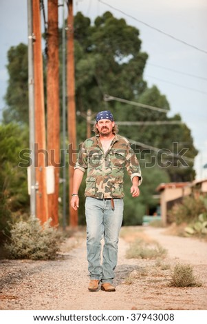 Rugged man in camoflauge walking on dirt road