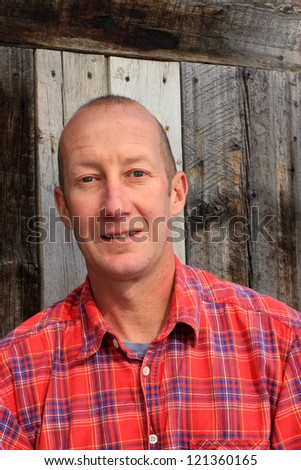 Rugged man in plaid shirt with a barn wood background. #121360165
