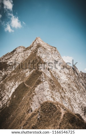 Rugged mountain ridge with hiking trails leading to a high altitude alpine summit on a steep rocky pinnacle peak against a blue sky with vignette