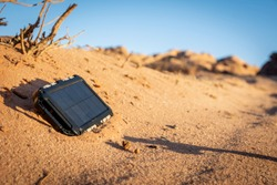 Rugged power bank with solar panel charging electricity in the nature and sand of the desert during a sunny day. Outdoor adventure ensuring charging of your mobile devices.