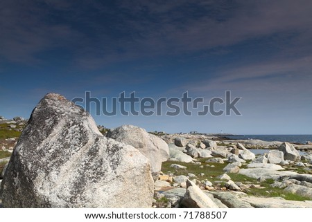 Rugged rocky coast with a distant lighthouse - stock photo