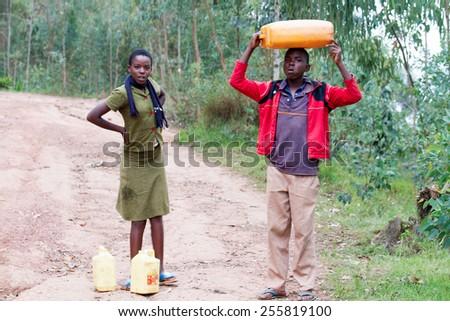 RUHENGERI, RWANDA-NOVEMBER 15, 2013: unidentified children brings a cans of potable water in Ruhengeri, Rwanda, November 15, 2013