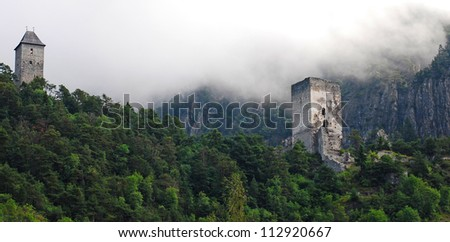 ruin in the mountains surrounded by forest and haze