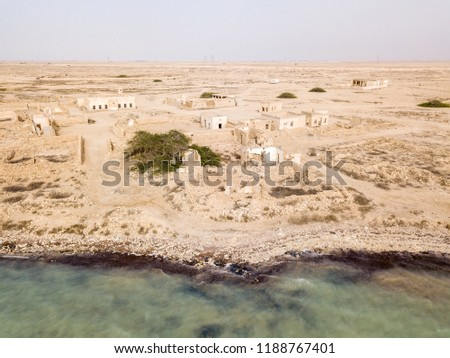 Ruined ancient old Arab pearling and fishing town Al Jumail, Qatar. The desert at coast of Persian Gulf. Abandoned mosque with minaret. Deserted village. Aerial drone photography, bird's eye view.