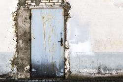 Ruined brick wall with closed steel door