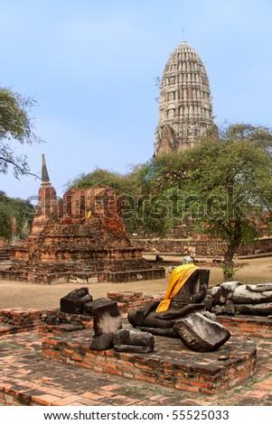 Ruined Buddha statue near chedi and prang within Wat Ratchaburana temple complex at Ayutthaya, Thailand. - stock photo