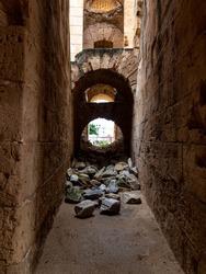 Ruined corridor with fallen stones of the Amphitheatre of El Jem, Tunisia.