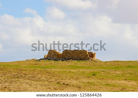 Ruined house in a desert under a clouds